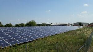 Solarpark, Module in Sonne, blauer Himmel, im Hintergrund Industriegebäude