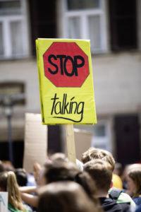 Demonstranten halten ein Schild mit der Aufschrift Stop talking hoch; Foto: Markus Spiske, unsplash