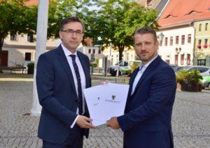 Bürgermeister Sven Hause (im Bild rechts) nimmt auf dem Marktplatz der Saalestadt die Fördermittelbescheide von Staatssekretär Thomas Wünsch entgegen.